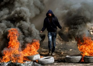 A Palestinian protestor carries car tires in a fire during clashes with Israeli security forces, following a demonstration in the village of Kfar Qaddum, near Nablus, in the occupied West Bank on January 13, 2017. / AFP PHOTO / JAAFAR ASHTIYEH